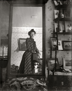 Black and white photo of a mirror showing a woman circa 1900 holding a camera